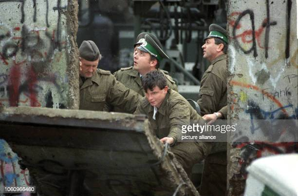 Border police forces close a hole people stemmed into the Berlin Wall, 11 November 1989. Under the people's pressure the GDR opened its borders on...