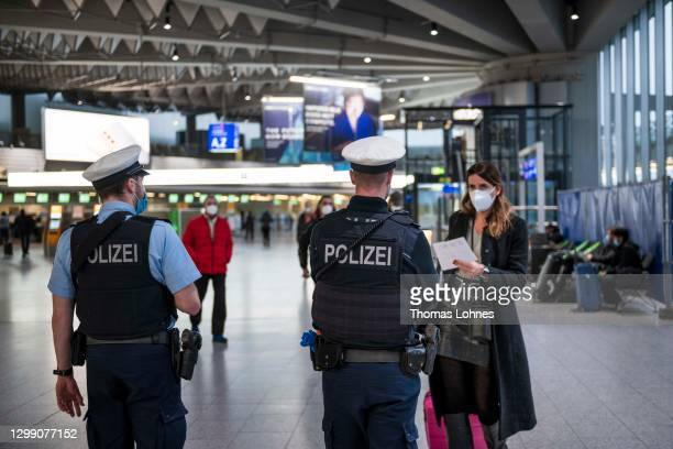 Border Police officers explain a passenger the way in the Terminal 1 of the Frankfurt Airport on January 28, 2021 in Frankfurt, Germany. Border...
