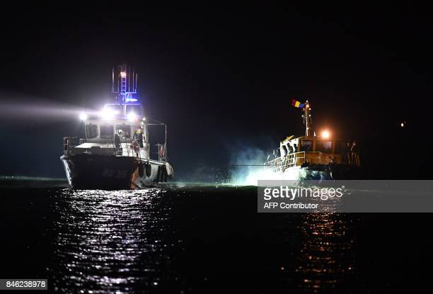 A border police ship draws a migrants transporting vessel to Midia Port at Black Sea coast next to Navodari city on September 13 2017 EU member...