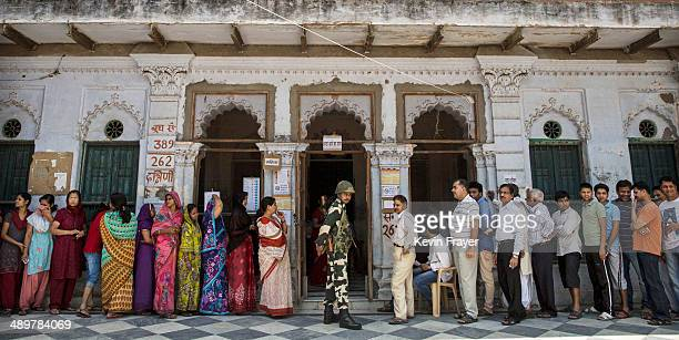 Border Security Force officer stands guard as Indians wait in line to vote at a polling station on May 12 2014 in Varanasi India Indians voted in the...