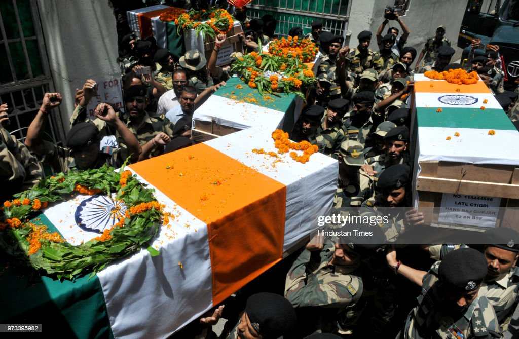 Border Security Force (BSF) personnel carry the coffins of four BSF personnel, killed in cross border firing, after a wreath laying ceremony at Paloura BSF Headquarters on June 13, 2018 in Jammu, India.