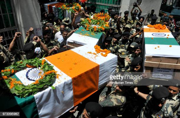 Border Security Force personnel carry the coffins of four BSF personnel killed in cross border firing after a wreath laying ceremony at Paloura BSF...