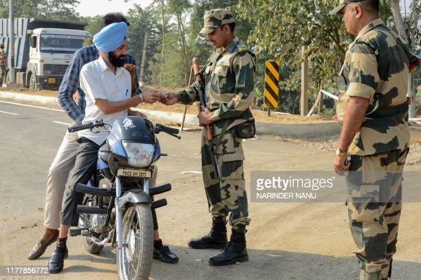Border Security Force personnel check identity documents of motorcyclists at Dera Baba Nanak some 50 kms from Amritsar on October 24 2019 India and...