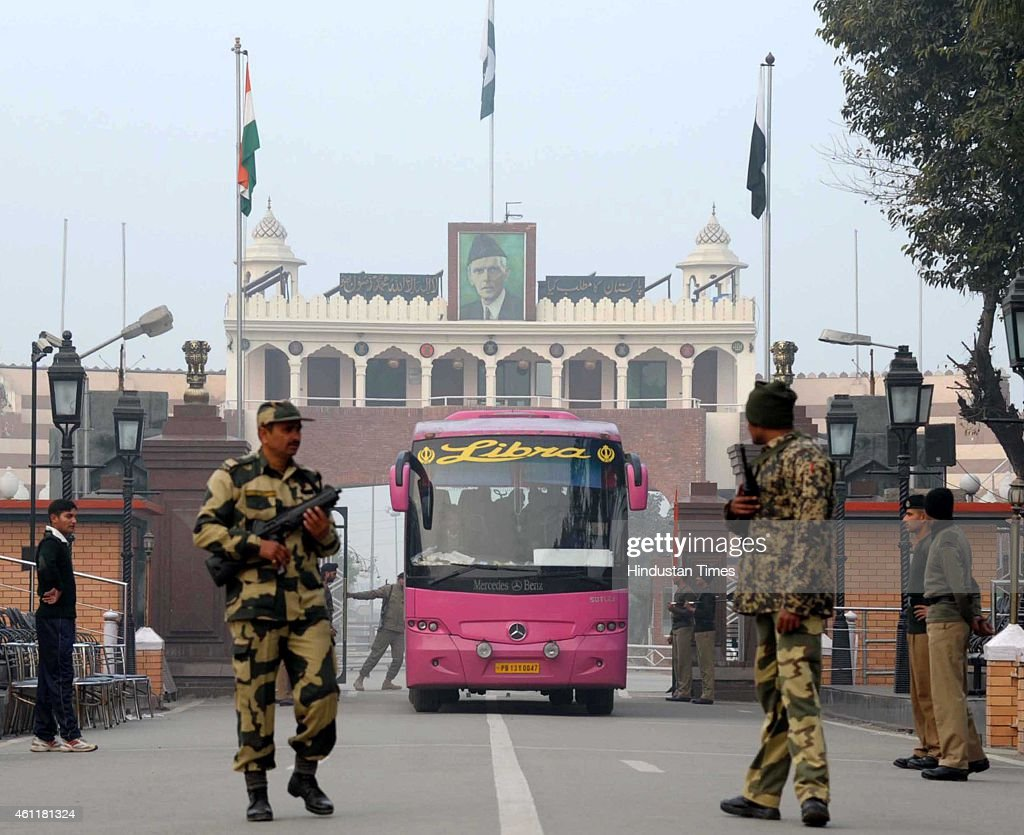 Border Security Force personnel escort the DelhiLahore bus as it crosses the IndiaPakistan border at Attari on January 8 2015 in Amritsar India...