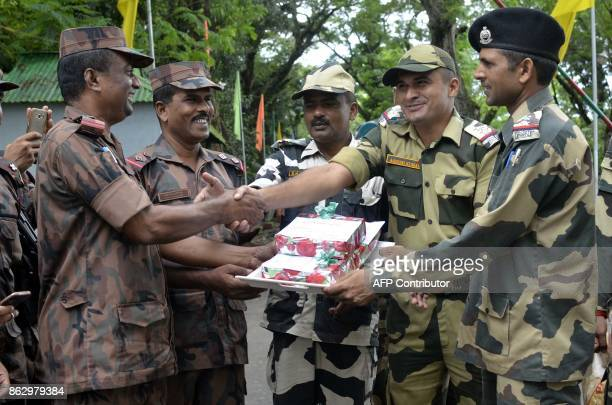 TOPSHOT Border Security Force personnel exchanges sweets with Border Guard of Bangladesh personnel during Diwali celebrations at India Bangladesh...