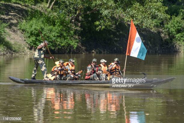 Border Security Force personnel keep a vigil on a boat during a patrol on the Gomati river near IndiaBangladesh border ahead of India's 73rd...