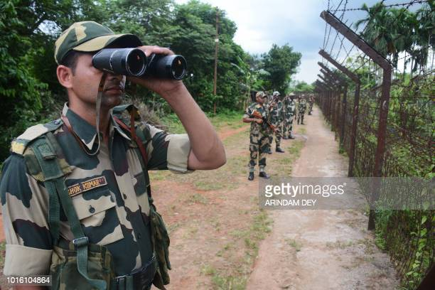A Border Security Force personnel patrols near the India Bangladesh fencing border ahead of 72nd Independence Day celebrations at Lankamura village...