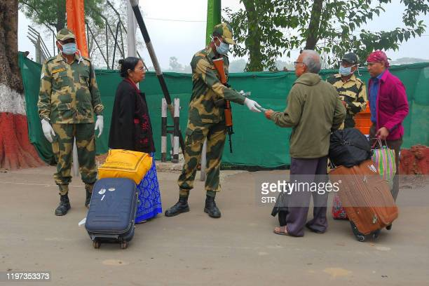 Border Security Force personnel wearing protective face masks and gloves check the passports of people travelling from Bangladesh to India at Akhura...