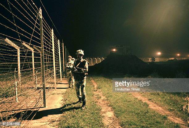Border Security Force soldiers standing guard during a night patrol near the fence at the IndiaPakistan International Border at the outpost of...