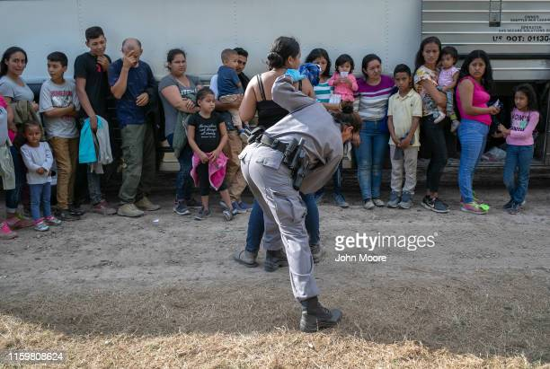 A border security officer searches immigrants before transferring them by bus to the McAllen Border Patrol facility on July 02 2019 in Los Ebanos...