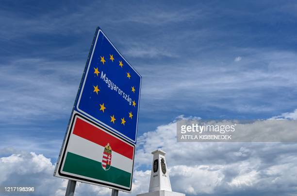 Border sign stands next to triangular stone column marking the spot where the borders of Hungary, Romania, and Serbia meet in Kubekhaza near Szeged...