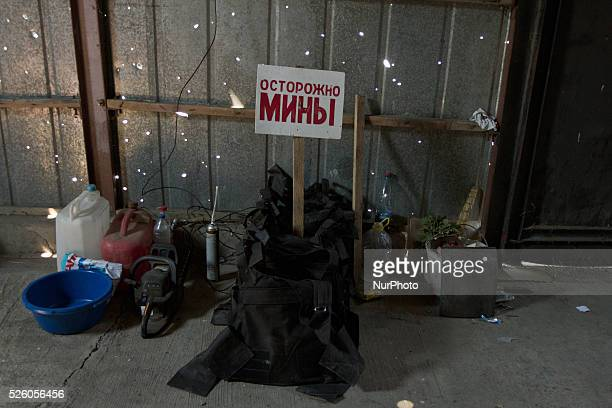 Border Troops' belongings lay with a warninging about landmines sign on the ground of a bulletridden shed at Novoazovsk Border crossing point on...