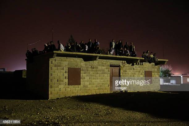 Border village of Alizar residents keep guard during the night and wait in fear from mortar fired from Islamic State fighters as they tightened their...