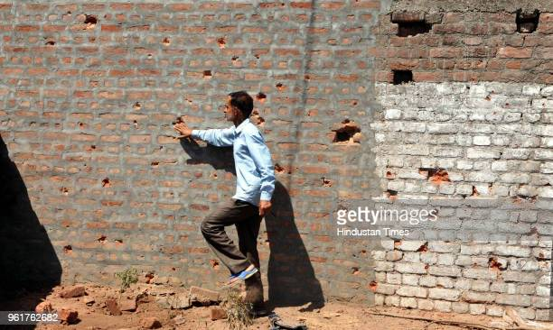 A border villager inspects the pockmarked wall of a building damaged by shelling from the Pakistani side of the border in Nanga village of Ramgarh...