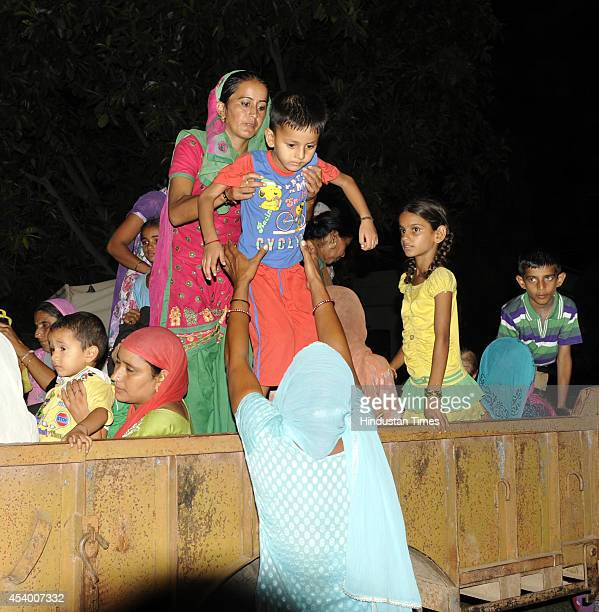 Border villagers along with children carry their belongings coming down from a trolly as they leave their homes to take shelter in a comunity hall at...