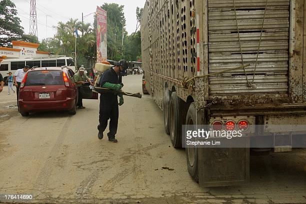 Border worker sprays down a truck crossing from Honduras into Nicaragua.
