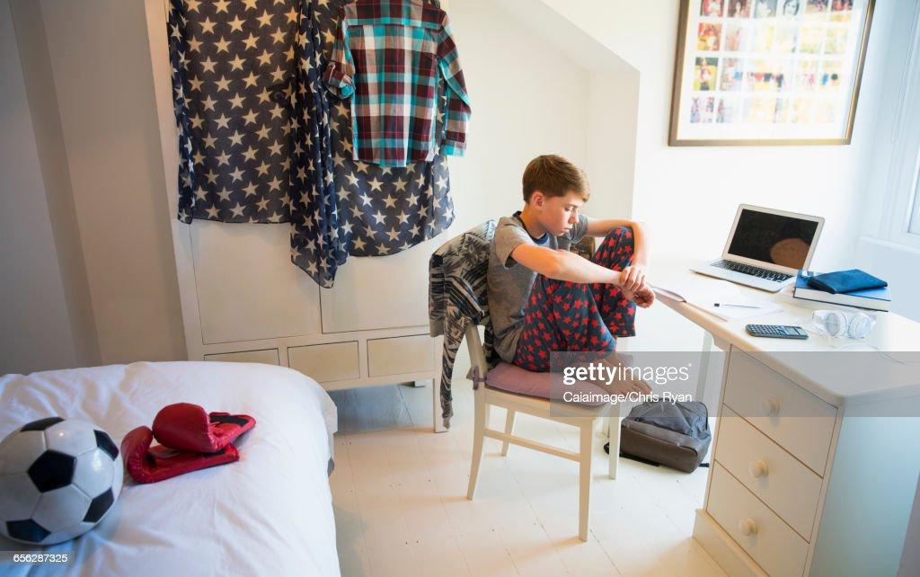 Bored Boy Doing Homework At Desk In Bedroom Stock-Foto ...