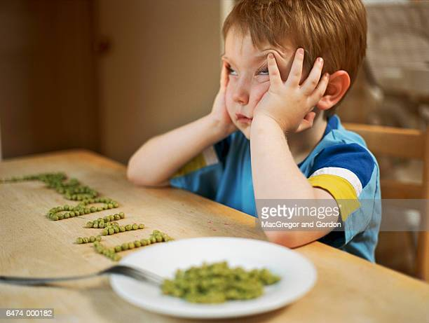 Bored Boy Playing with Peas