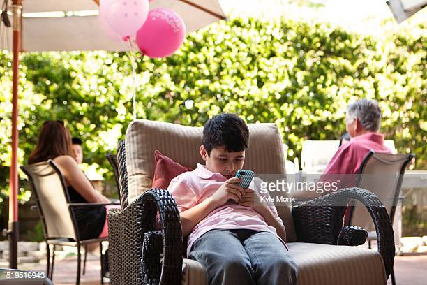 Bored boy using cell phone at party