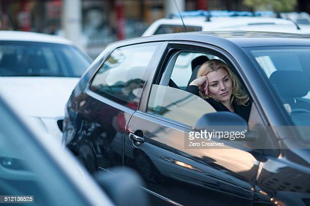 bored businesswoman driving in city traffic jam - traffico foto e immagini stock