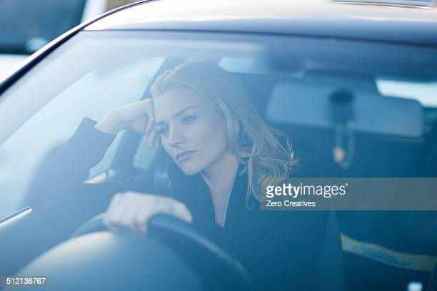 Bored businesswoman staring whilst driving in city traffic jam