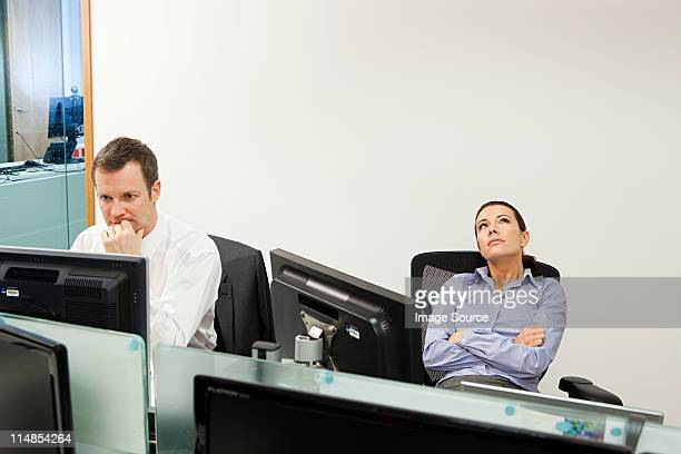 Bored businesswoman with male colleague in office