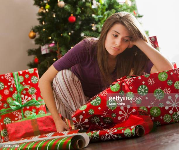 Bored Caucasian woman wrapping Christmas gifts