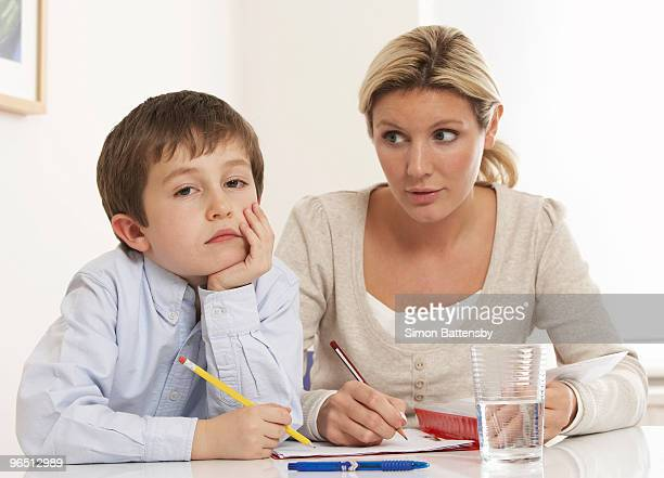 bored child with woman doing schoolwork