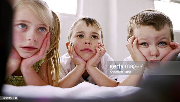 bored children watching television - hypnose photos et images de collection