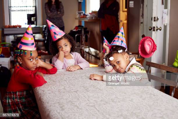 Bored children wearing party hats at table