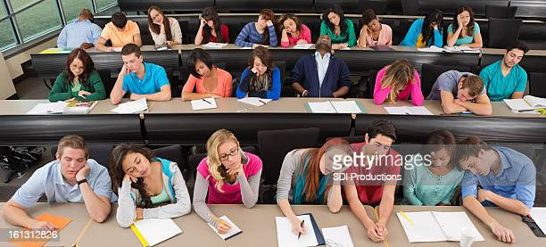 Bored college students asleep on desks in lecture hall classroom
