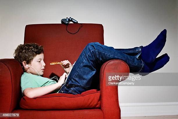 bored couch potato boy eating pizza - unhealthy living stock pictures, royalty-free photos & images