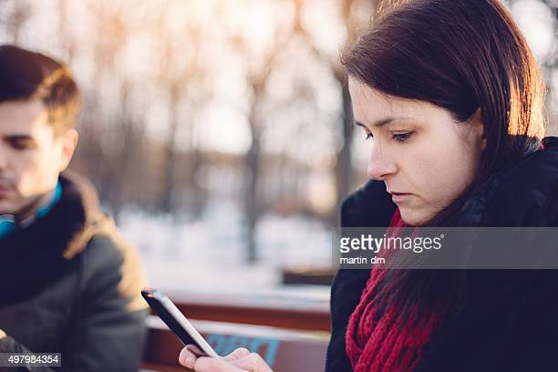 Bored couple texting outside