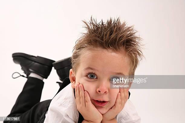 Niño atractivo orificio de sujeción de cabeza con las manos en la cara
