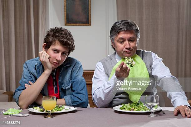 A bored father and son at the dinner table