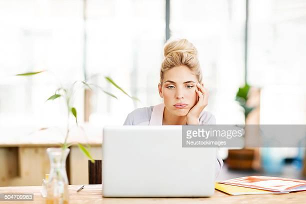 Empresario aburrido mujer usando una computadora portátil en el mostrador