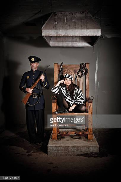 bored female prisoner in electric chair - electric chair stock photos and pictures