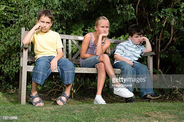 Bored kids on a park bench