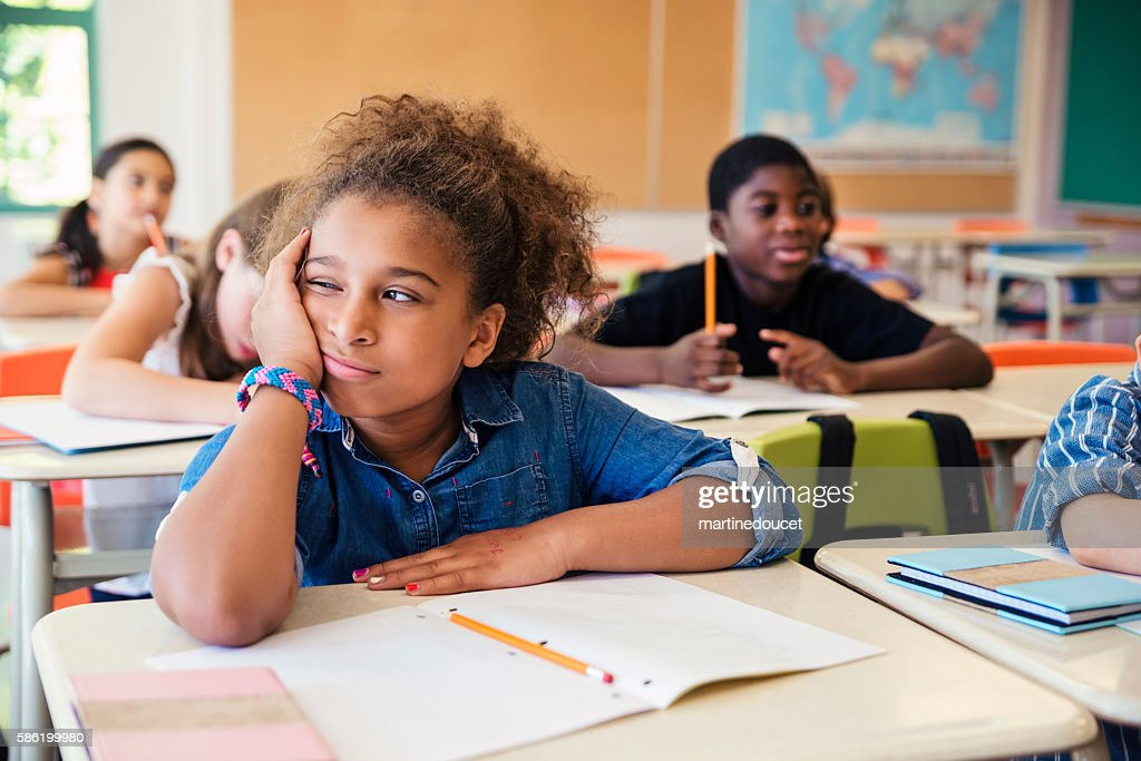 Bored little girl in elementary classroom. : Stock Photo