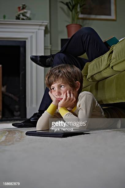Bored looking boy using tablet computer under sofa