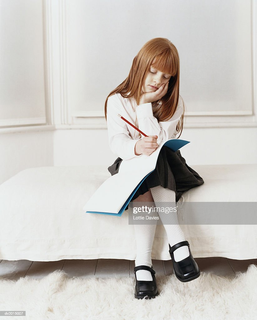 Bored Looking Primary Schoolgirl in Uniform Sits on Bed Writing in an Exercise Book : Stock Photo