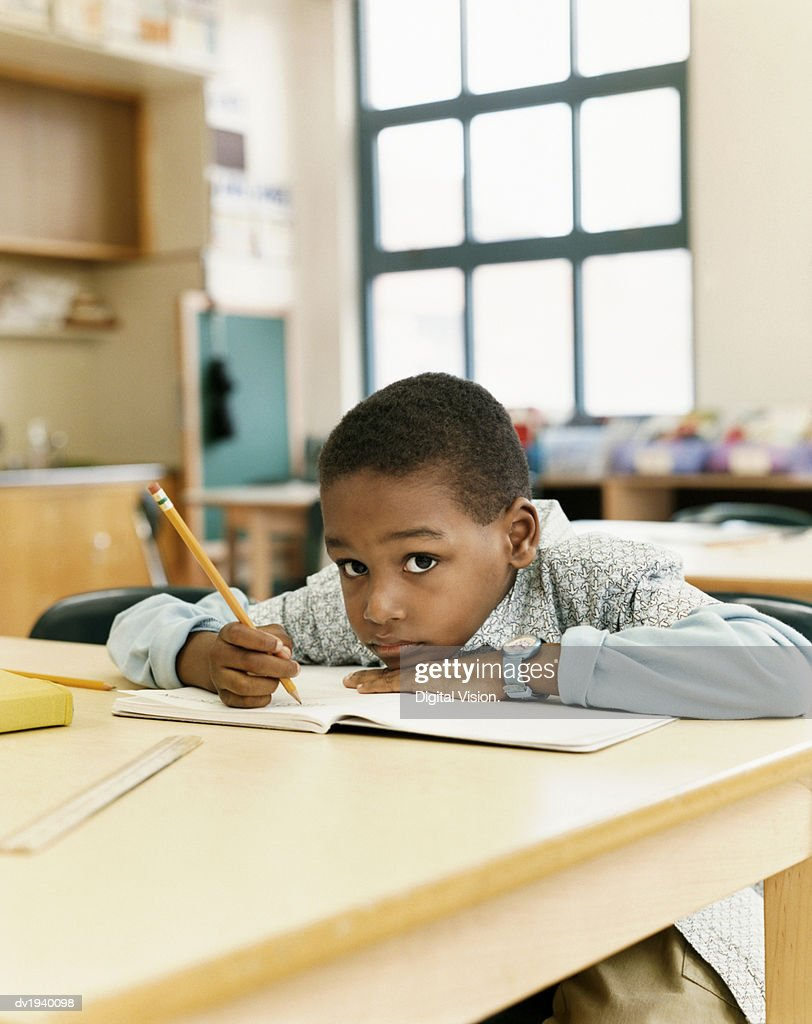 Bored Looking Schoolboy Sitting at a Table and Resting His Head on a Exercise Book : Stock Photo