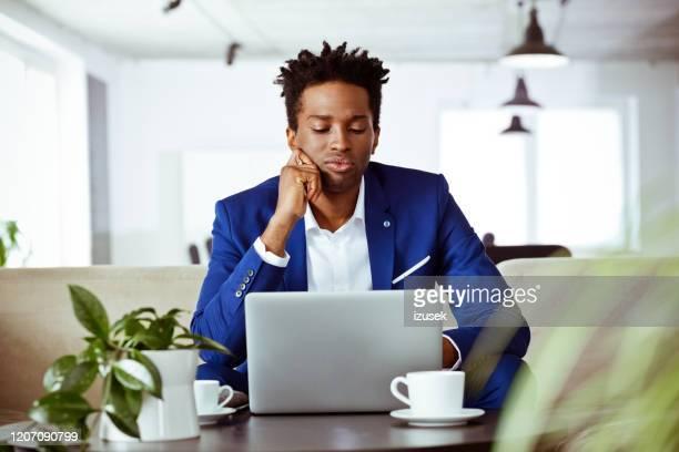consejero financiero masculino aburrido mirando portátil - izusek fotografías e imágenes de stock