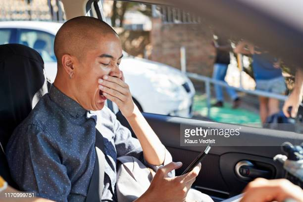 bored male hipster yawning while using smart phone - bad student stock pictures, royalty-free photos & images