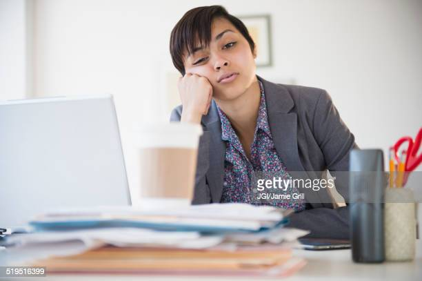 Bored mixed race businesswoman sitting at office desk