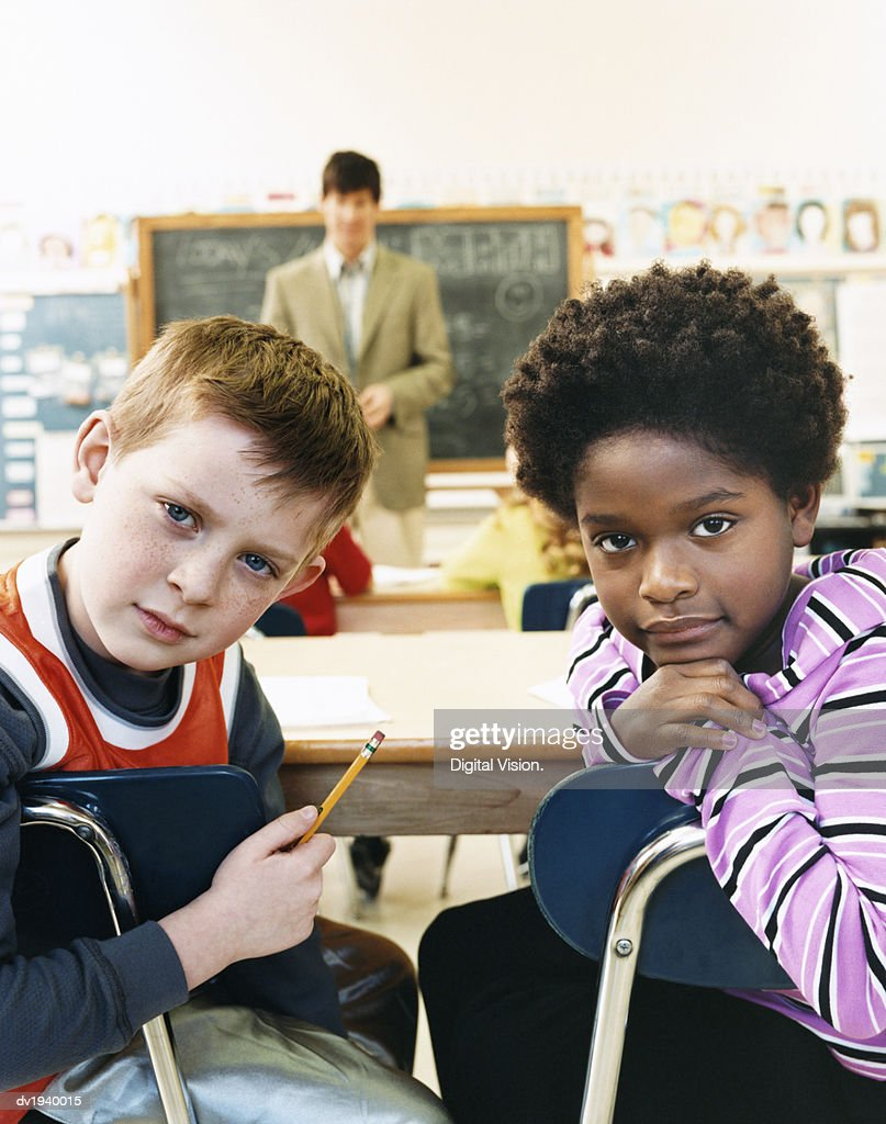 Bored Primary Schoolboy and Schoolgirl Sitting Behind Desks in a Classroom and a Teacher in the Background : Stock Photo