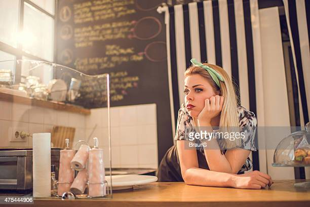 Bored retro styled female worker waiting for her customers.
