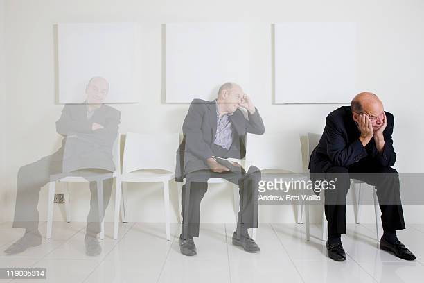 bored senior man passing time in a waiting room - fading stock pictures, royalty-free photos & images