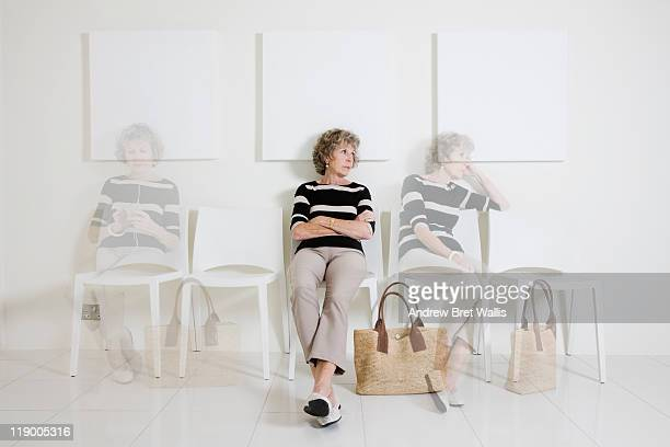 bored senior woman passing time in a waiting room - fading stock pictures, royalty-free photos & images