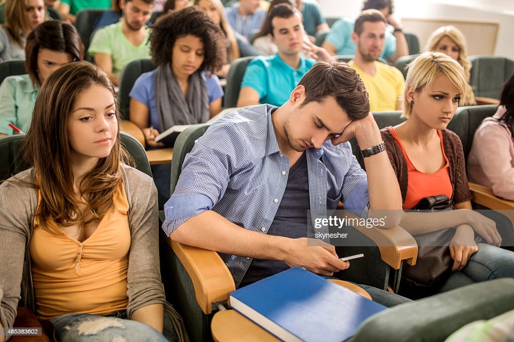Bored student text messaging on cell phone during a lecture. : Bildbanksbilder